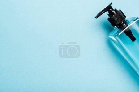 Photo pour Vue du dessus du désinfectant pour les mains en flacon transparent avec distributeur sur fond bleu - image libre de droit