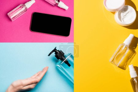 Photo for Collage of female hand near sanitizer, hand cream and smartphone near antiseptic liquid on multicolored bakground - Royalty Free Image