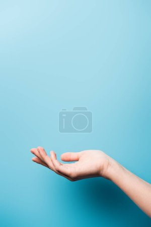 Photo pour Vue recadrée de la main femelle avec paume ouverte sur bleu - image libre de droit