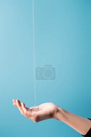 Photo pour Vue recadrée de la main féminine sous le savon liquide coulant sur bleu - image libre de droit