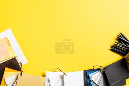 Photo for Top view of painting and blank samples near color pencils isolated on yellow - Royalty Free Image