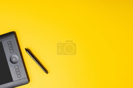 Photo for Top view of drawing tablet and stylus on yellow - Royalty Free Image