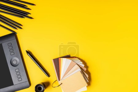Photo for Top view of stylus, drawing tablet colorful palette and pencils on yellow - Royalty Free Image