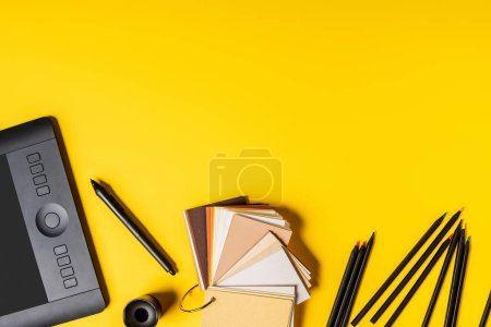 Photo for Top view of drawing tablet, colorful palette and pencils near stylus on yellow - Royalty Free Image