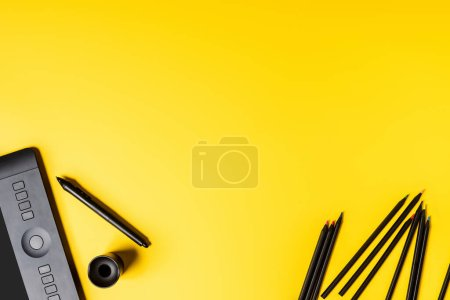Photo for Top view of drawing tablet and pencils near stylus on yellow - Royalty Free Image