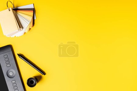 Photo for Top view of drawing tablet, palette and color pencils near stylus on yellow - Royalty Free Image
