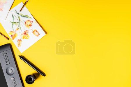 Photo pour Vue du dessus de la tablette de dessin, fleurs dessinées sur peintures et pinceaux près du stylet sur jaune - image libre de droit