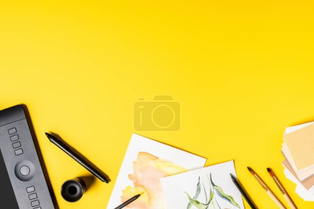 Photo for Top view of drawing tablet, paintings and paintbrushes near stylus and color pencils on yellow - Royalty Free Image