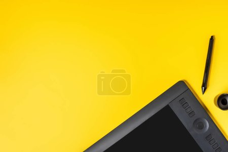 top view of drawing tablet near stylus holder and stylus on yellow