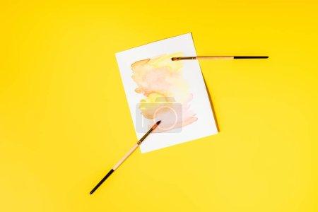 Photo pour Vue de dessus des pinceaux près de la peinture sur jaune - image libre de droit