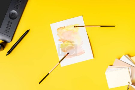 Photo for Top view of drawing tablet, painting and paintbrushes near stylus and color palette on yellow - Royalty Free Image