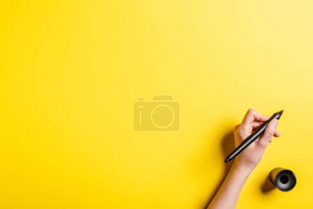 cropped view of designer holding stylus near stylus holder on yellow
