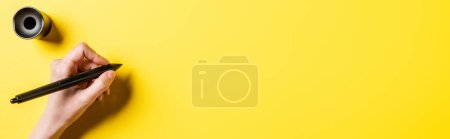 Photo for Horizontal image of designer holding stylus near stylus holder on yellow - Royalty Free Image