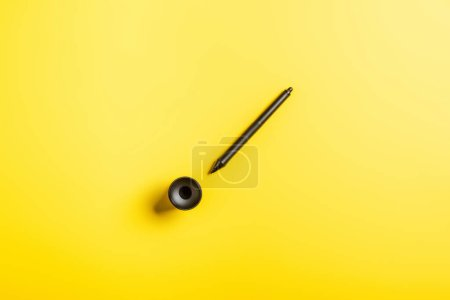 Photo for Top view of black stylus near holder on yellow - Royalty Free Image