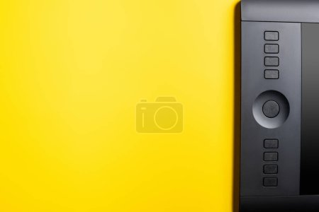 top view of black drawing tablet on yellow