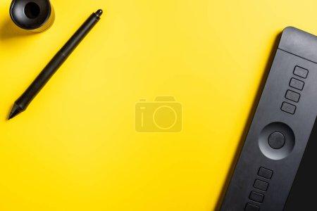 Photo pour Vue du dessus de la tablette de dessin moderne, stylet et support sur jaune - image libre de droit