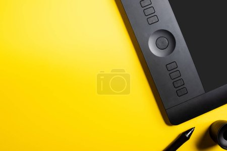 Photo pour Vue du dessus de la tablette de dessin moderne et stylet noir sur jaune - image libre de droit