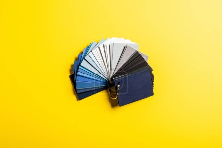 Photo for Top view of palette with blue, grey and black colors on yellow - Royalty Free Image