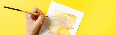 Photo pour Récolte horizontale de l'artiste tenant le pinceau près de la peinture sur jaune - image libre de droit