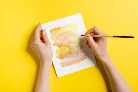 Photo for Cropped view of woman holding paintbrush near painting on yellow - Royalty Free Image