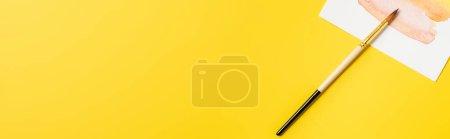 Foto de Orientación panorámica del pincel cerca de la pintura aislada en amarillo - Imagen libre de derechos