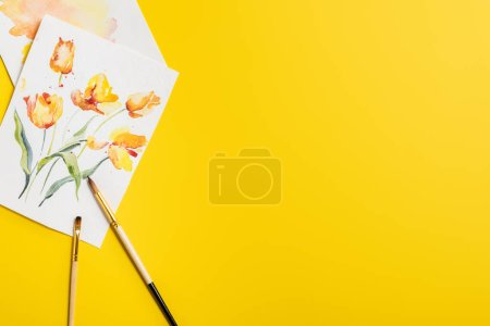 Photo for Top view of paintbrushes near creative paintings with drawn flowers isolated on yellow - Royalty Free Image