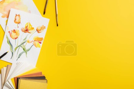 Photo for Top view of paintbrushes near paintings with drawn flowers and color palette on yellow - Royalty Free Image