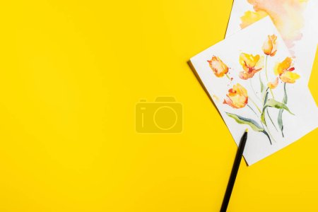 Photo for Top view of paintbrush near paintings with drawn flowers on yellow - Royalty Free Image