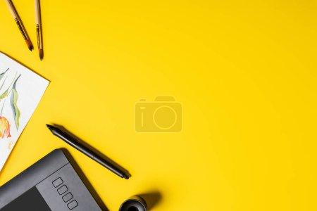 Photo pour Vue du dessus des pinceaux près de la peinture, tablette de dessin, support et stylet sur jaune - image libre de droit