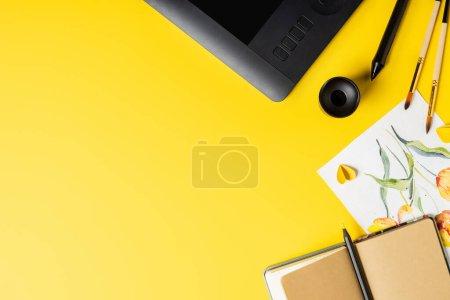 Photo pour Vue du dessus des pinceaux près de la peinture, tablette de dessin, carnet et stylet sur jaune - image libre de droit