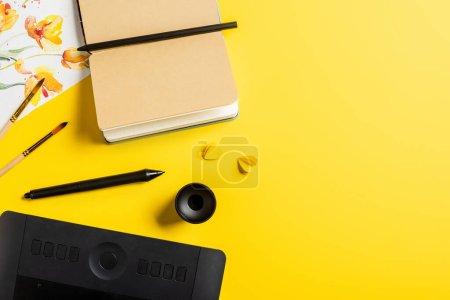 Photo pour Vue du dessus des pinceaux près de la peinture, tablette de dessin, carnet vierge et stylet sur jaune - image libre de droit