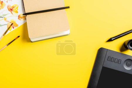 Photo pour Vue du dessus des pinceaux près de la peinture, carnet vierge, tablette de dessin et stylet sur jaune - image libre de droit