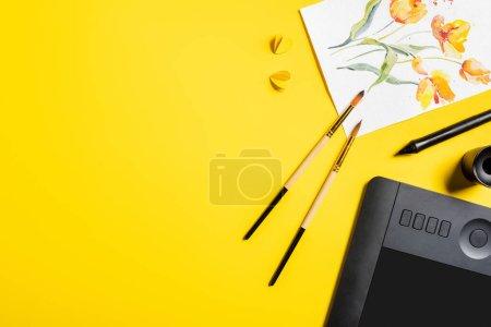 Foto de Vista superior de pinceles cerca de la pintura, elementos de corte de papel, tableta de dibujo y lápiz en amarillo - Imagen libre de derechos