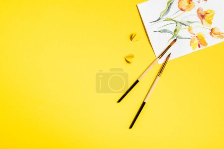 Photo for Top view of paintbrushes near drawn flowers on painting and paper cut elements on yellow - Royalty Free Image