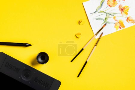 top view of paintbrushes near drawn flowers on painting, paper cut elements, drawing tablet and stylus on yellow