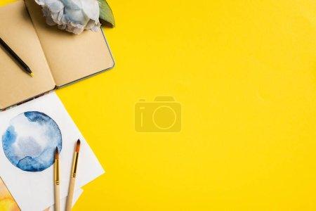 Photo pour Vue de dessus des pinceaux près des peintures, carnet vierge et fleur sur jaune - image libre de droit