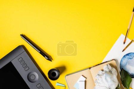 Photo pour Vue du dessus des pinceaux près de la peinture, tablette de dessin, stylet, carnet et fleur sur jaune - image libre de droit