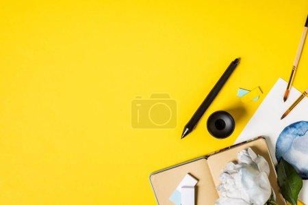 Photo pour Vue du dessus des pinceaux près de la peinture, stylet noir, carnet et fleur sur jaune - image libre de droit