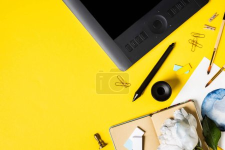 Photo pour Vue du dessus de la peinture, tablette de dessin avec écran blanc, clips, stylet, cahier et fleur sur jaune - image libre de droit