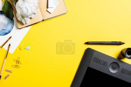 Photo pour Vue du dessus de la tablette de dessin avec écran blanc, clips, stylet, peinture, ordinateur portable et fleur sur jaune - image libre de droit
