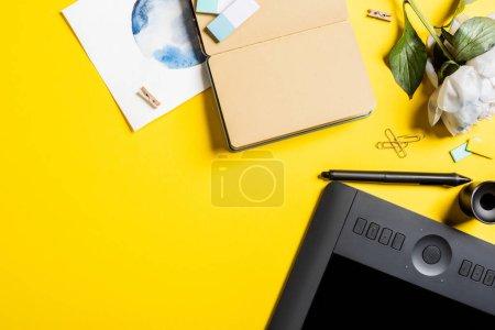 Photo pour Vue du dessus de la tablette de dessin avec écran vierge, clips, stylet, peinture, bloc-notes vierge et fleur sur jaune - image libre de droit