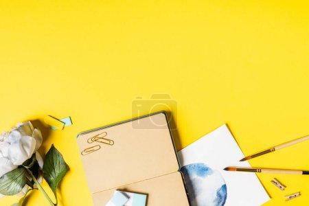 Photo pour Vue de dessus des pinceaux, clips, peinture, carnet vierge et fleur sur jaune - image libre de droit