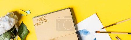 Photo pour Concept panoramique de pinceaux, clips, peinture, carnet vierge et fleur sur jaune - image libre de droit