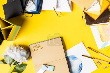 Photo pour Vue de dessus des pinceaux, clips, peintures, carnet vierge, fleur et palette colorée sur jaune - image libre de droit