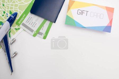 Photo pour Vue du dessus de la carte près de toy plane, passeport et carte cadeau sur fond blanc - image libre de droit
