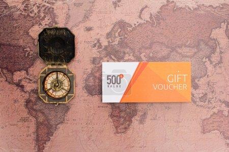 Photo pour Vue du dessus du bon cadeau avec 500 lettres de valeur et boussole sur la surface de la carte - image libre de droit