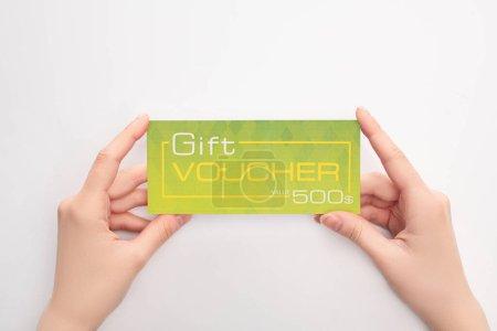Photo pour Vue recadrée de la femme tenant un chèque-cadeau vert avec lettrage de valeur sur fond blanc - image libre de droit