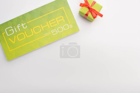 Top view of gift voucher and present on white background with copy space