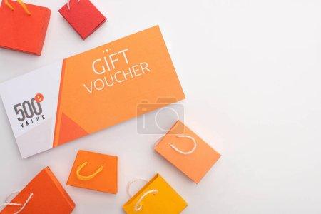 Photo pour Vue du dessus du bon cadeau près des sacs à provisions de jouets sur la surface blanche - image libre de droit