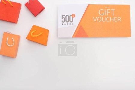 Photo pour Vue du dessus du bon cadeau avec 500 dollars lettrage de valeur près de jouets sacs à provisions sur fond blanc avec espace de copie - image libre de droit